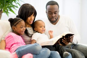 father leading family in Bible study