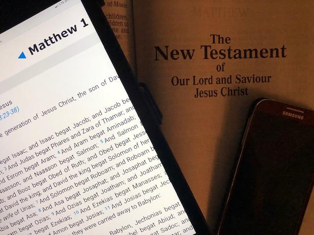 Picture of Tablet, phone and hardcopy of Bible opened to New Testament title page